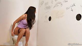 Eliza enjoying a gloryhole experience in a toilet room